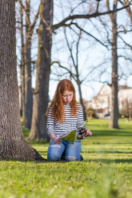 girl reads book outside under tree