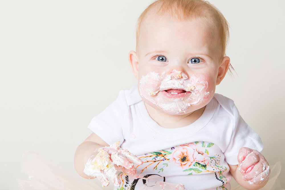 cake smash girl with cake on face
