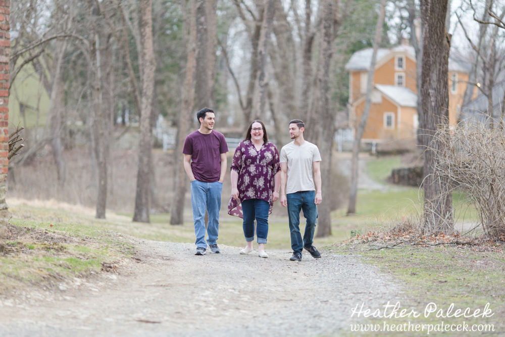 three people walk towards camera in woods