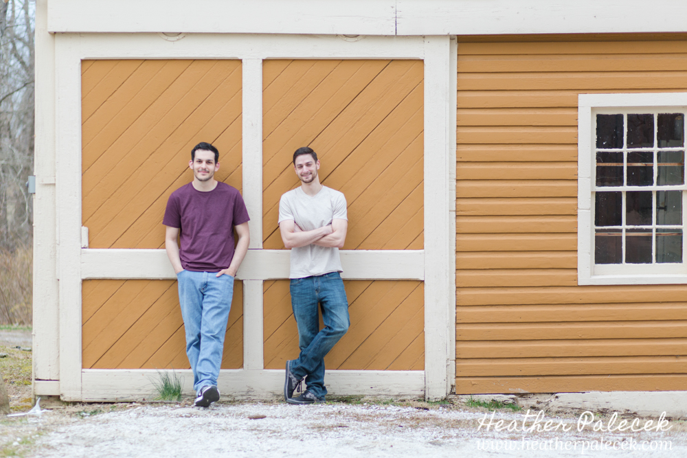 two men pose on yellow wall