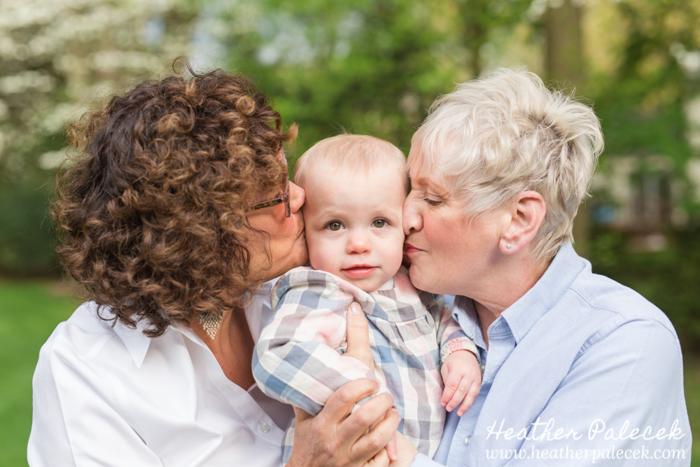 two grandmothers kiss their granddaughter