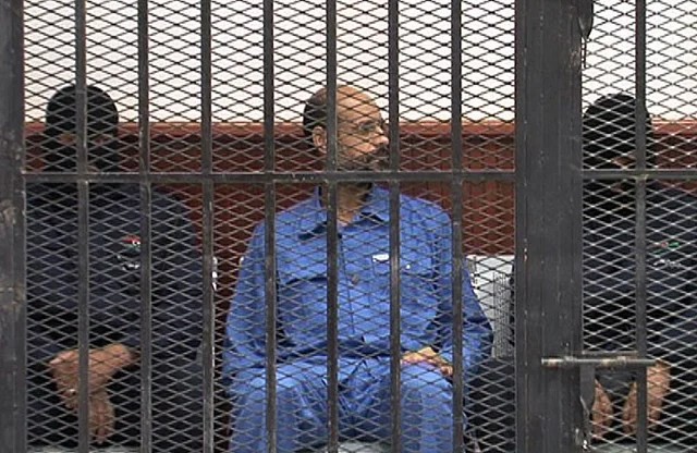 <p>Saif al-Islam, son of deposed strongman Muammar Gaddafi, sits behind bars during a court session in Zintan, Libya on May 2, 2013.</p>