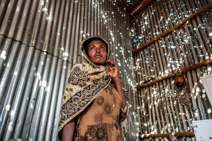 A woman stands in a metal sheet room that was damaged by shelling in Humera town, Tigray region, Ethiopia, on November 22, 2020. In that residential compound, two women and an elderly man were killed by shelling and gunfire, and two women were wounded.