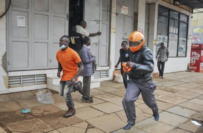 People in Uganda's capital Kampala flee on November 18, 2020 during clashes between security forces and demonstrators protesting the arrest of opposition candidate Robert Kyagulanyi for allegedly breaching Covid-19 regulations by mobilizing large crowds for his campaign rallies.