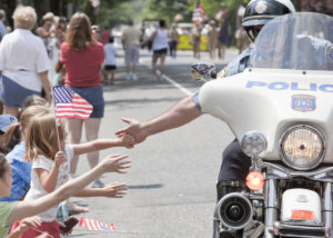 motorcycle cop high fiving kids in a parade