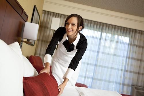 female hotel housekeeper making the bed