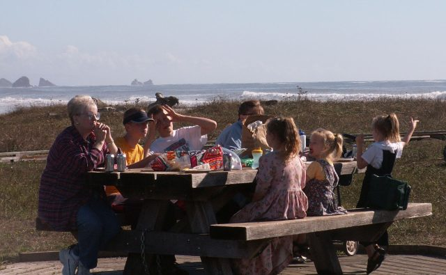 picture of family at picnic table by the ocean