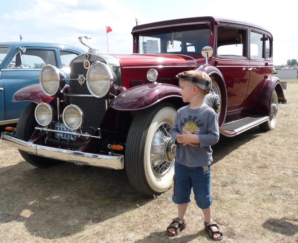 picture of Brock standing in front of old Cadillac