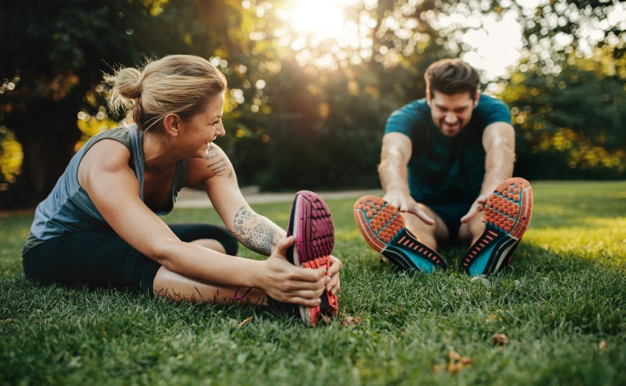 Happy young man and woman stretching in the park. Smiling caucasian couple exercising in morning.