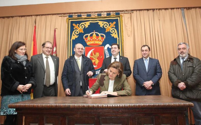 Cospedal firma en el libro de visitas del Ayuntamiento de Huete acompañada del alcalde y concejales