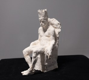 Plaster sculpture of a male nude, seated and wearing a crown, by Beth Carter titled King Minos in Chair