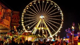 A shot of a fairground at night. Different coloured neon-lit stalls are in the foreground. A big wheel, lit white, takes up most of the picture