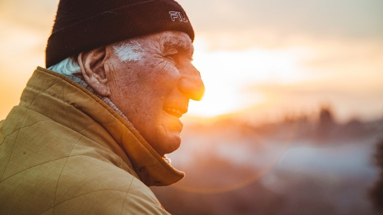 An older person with the setting sun behind them.