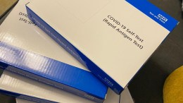 boxes containing lateral flow tests are stacked on a table. The boxes are white and blue and have an NHS logo