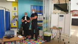 two people wearing masks stand in a pop-up Coronavirus testing booth. It is inside a rail interchange