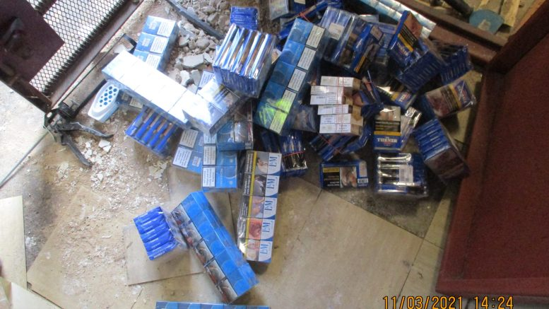 Packets of counterfeit cigarettes and tobacco sit on a concrete floor after being recovered from beneath a concrete floor