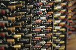 a large number of wine bottles are displayed in racks. Only their necks are visible