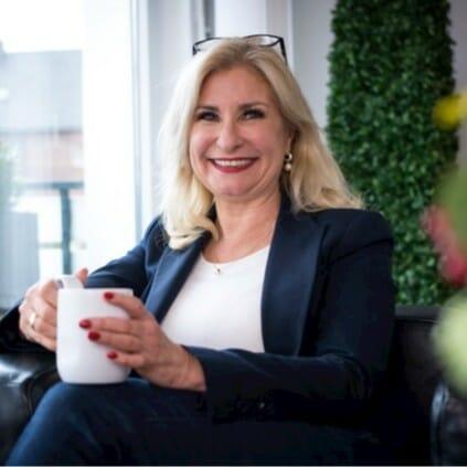 Blonde Frau mit Tasse in der Hand