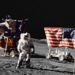 Harrison H Schmitt pilot of the lunar module stands on the lunar surface near the United States flag during NASAs final