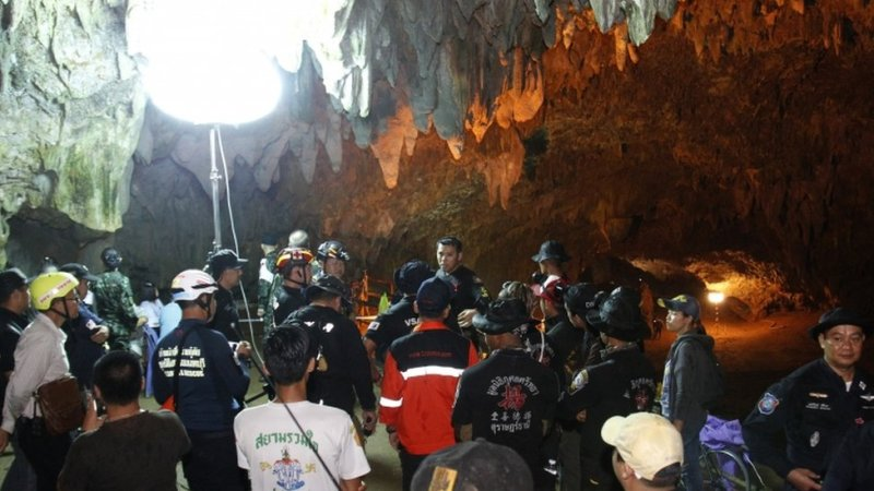 People gather in the cave system for a briefing, with special lighting equipment brought in