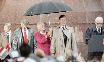 First Lady Barbara Bush holds an umbrella for President Bush as Hungarian President Bruno Straub speaks during the welcoming ceremony in Budapest, Hungary, Tuesday, July 11, 1989