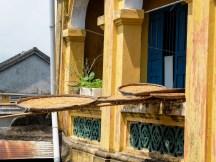 Местните хора усшат нудли в кошници, провесени от прозорците на древни сгради.