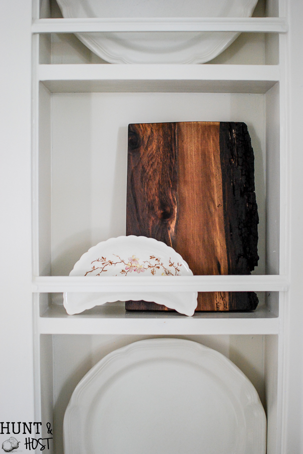 Kitchen cubbies get a makeover into a built in plate rack filled with gorgeous goodies like white and wood. White plates, cutting boards and antique tea and coffe pots. This simple DIY will help you transform small shelves into functional display space.