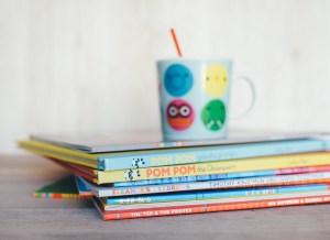 stack of children's books with child sippy cup on top