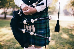 Man wearing kilt and holding bagpipe
