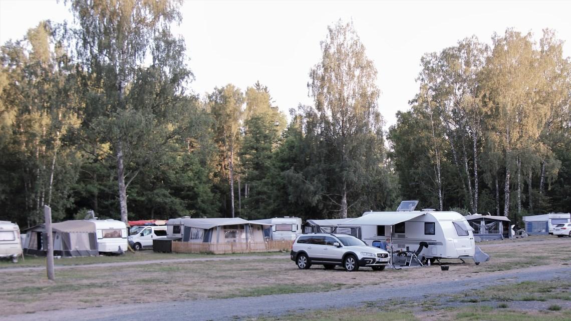 Campingplats med bil och husvagnar.