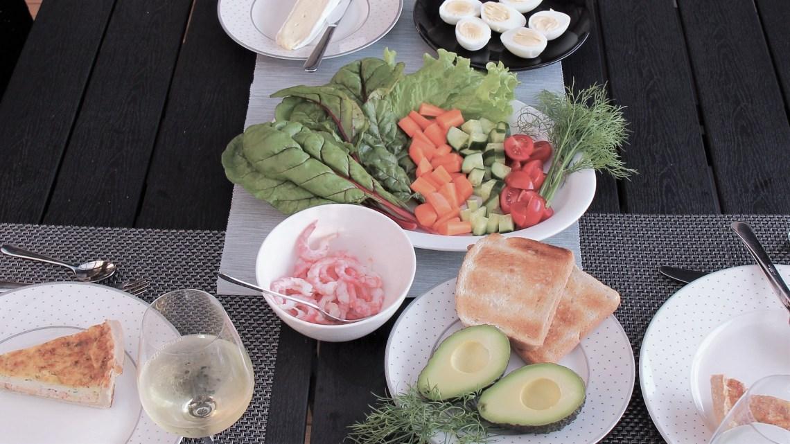 Middagsbord med mangold, räkor, skaldjurspaj och avokado.