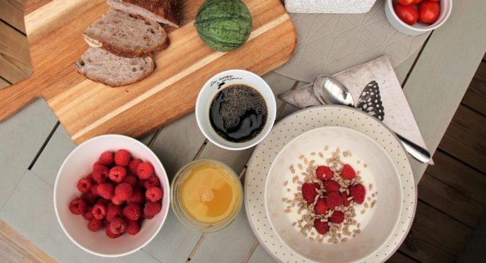 Frukostbord med hallon och valnötsbröd.