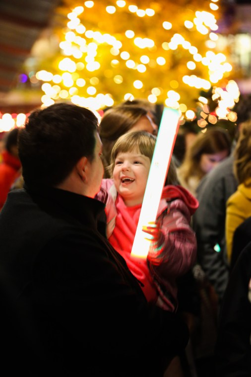 girl with Christmas lights in the background holding a light wand