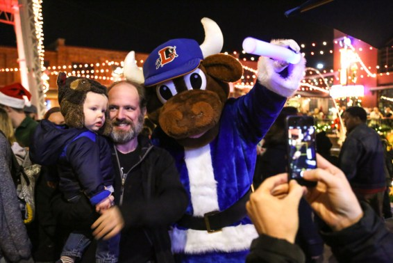 Wool-e Bull the Durham Bull's mascot in a blue Santa suit taking a photo with a family