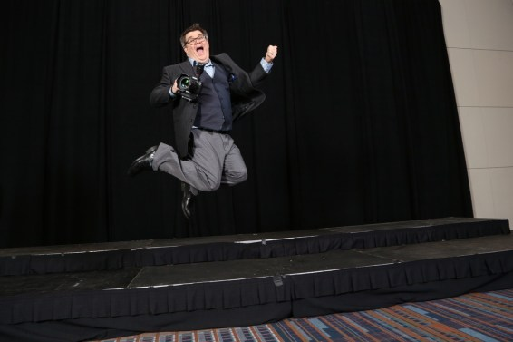 Ken Huth in a suit leaping from a stage with camera in hand