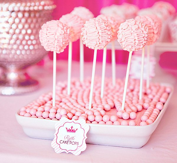 pink ruffle cake pops displayed in candy trays for a princess party