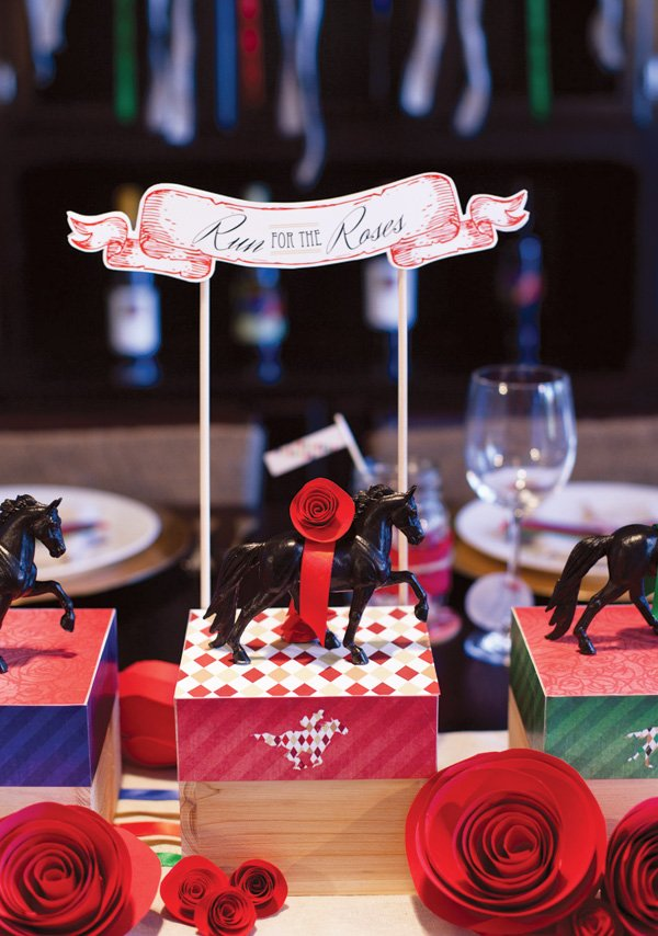 kentucky derby party centerpiece with red paper roses and toy horses