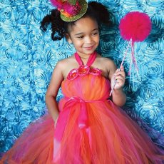 bright colored pink and orange tulle party dress costume with green fascinator hat on a little girl