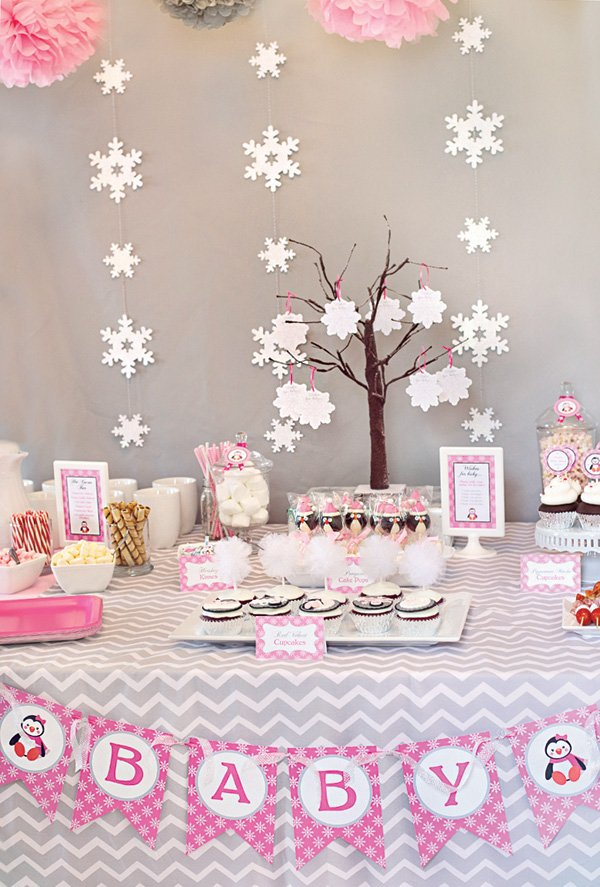 a pink and gray winter baby shower's dessert table with snowflake backdrop