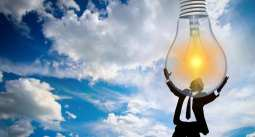 solar power - consumers in favour - man holding lightbulb to sky