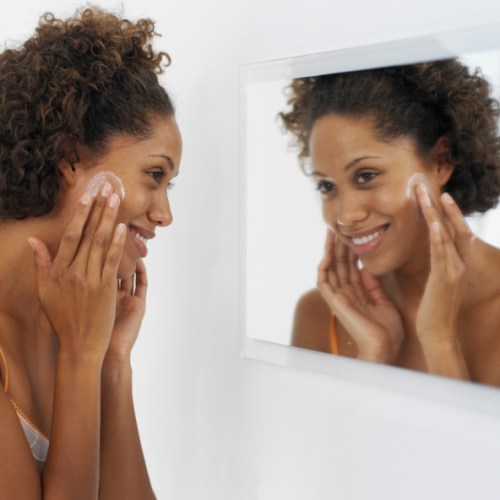 Side view of a woman applying face cream and looking in a mirror