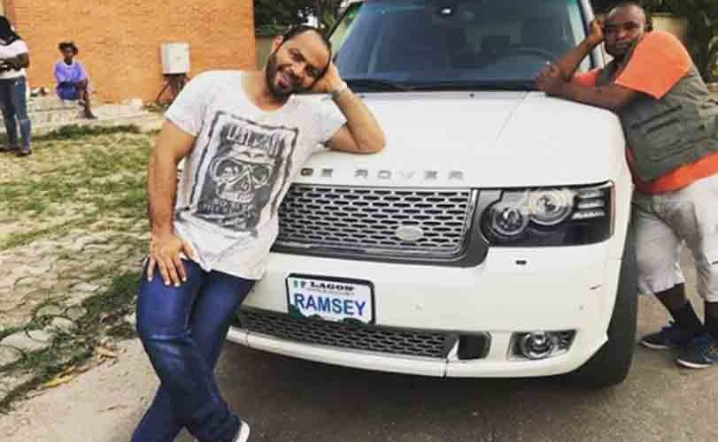 Veteran actor, Ramsey Noah poses next to his customized Range Rover
