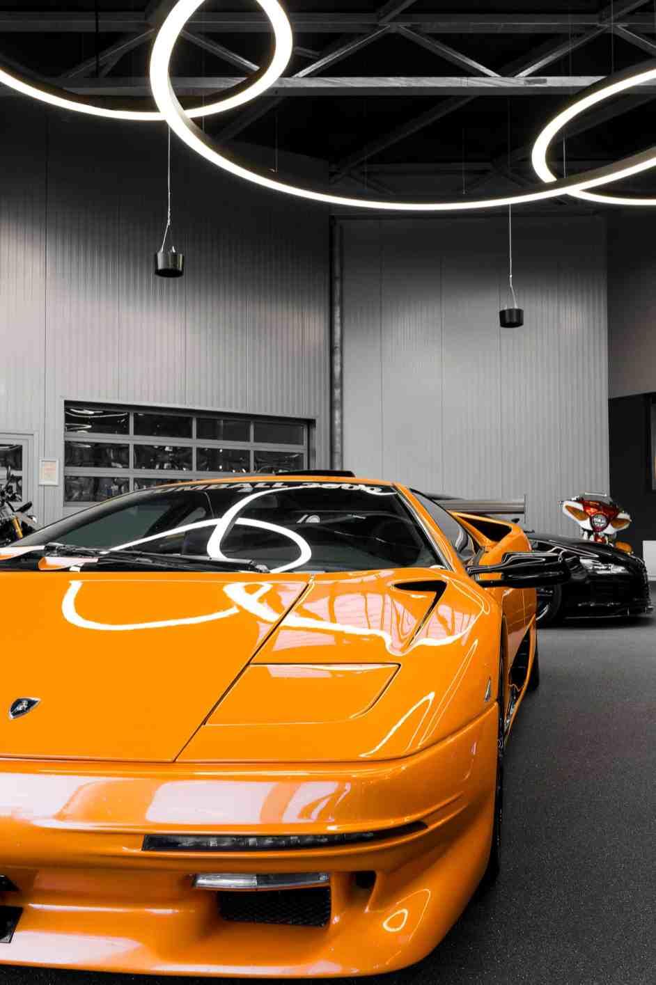 Mit einer warmweißen Farbtemperatur von 3.000 K zaubern die Lichtringe ein angenehm warmes Licht im Showroom, dass sich in den auf Hochglanz polierten Karosserien der Sportwagen widerspiegelt. (Bild: Prolicht)