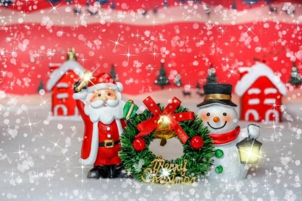 サンタさんと雪だるまがリースを持っています