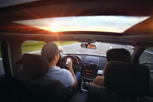 man driving looking at phone with woman