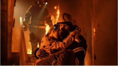 Fire fighter carrying a young girl down the stairs from a burning house