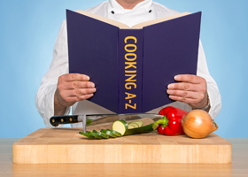 A chef reading a COOKING A-Z book