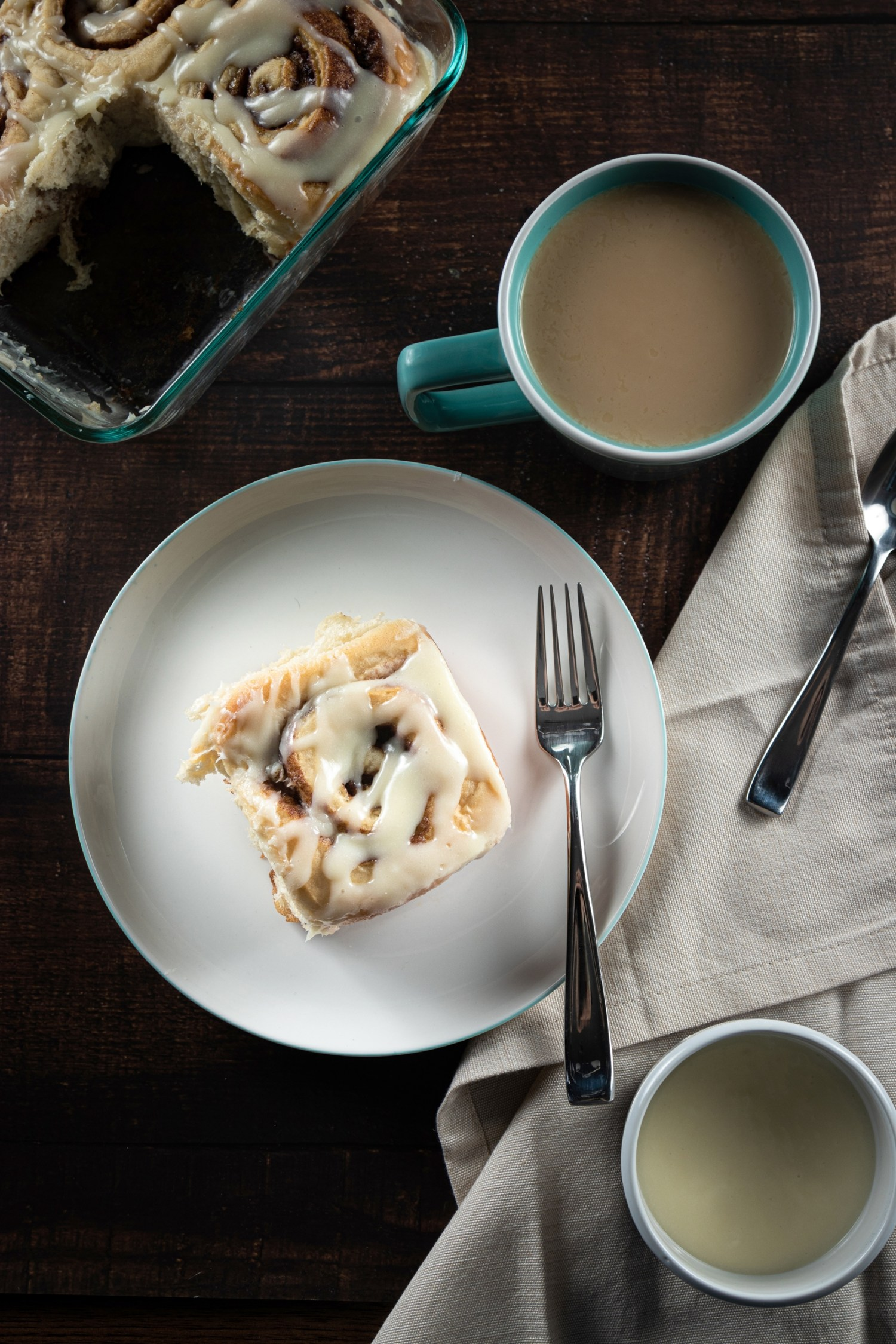 vertical shot of Cinnamon Bun on table with coffee and tray with missing cinnamon bun. Top down
