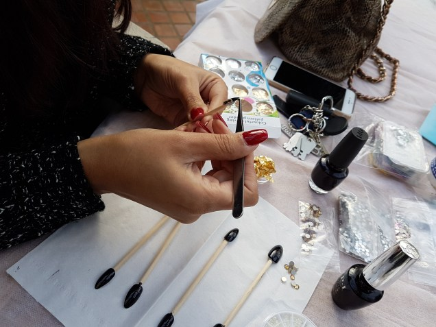 MUA Sonya Kaur working on a set of decorated false nails