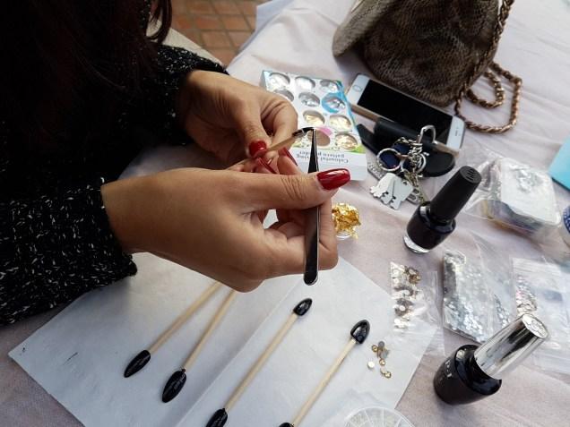 MUA Sonya Kaur working on a set of decorated false nails